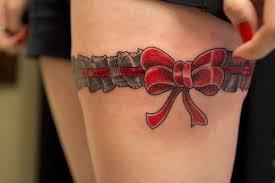 tiny gun tattoo on right thigh of
