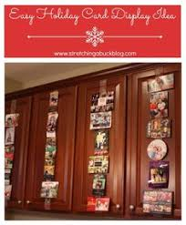 a creative way to display christmas cards with christmas ribbon