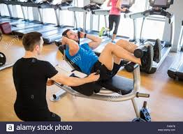 fit man doing sit ups with trainer stock photo royalty free image