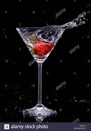 martini black martini drink splashing out of glass isolated on black background