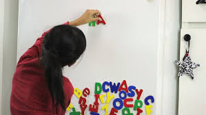 a seven year asian uses colorful fridge magnet