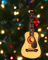 a folk guitar ornament and lights on a tree stock photo