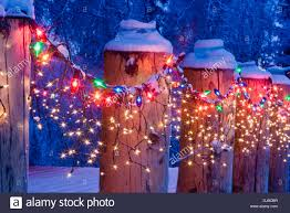 close up of christmas lights on log cabin porch railing at