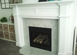 white wooden fireplace mantel with white tile around and black