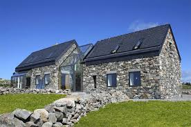 two stone cottages connected by a glass staircase rustic style