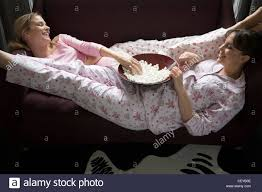 taken from above of two female friends wearing pyjamas eating