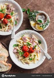 Mediterranean Style Food - tuna pasta with roasted tomatoes on a brown wooden background top