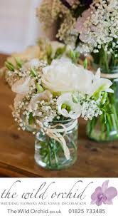 wedding flowers on a budget uk a trio of clear glass jam jars with raffia ribbon filled