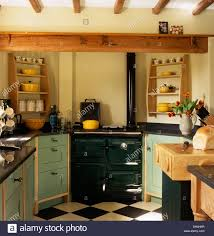 cottage kitchen furniture dark green range oven set between pale green fitted units in