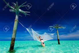 woman leaning on over water hammock in the middle of tropical