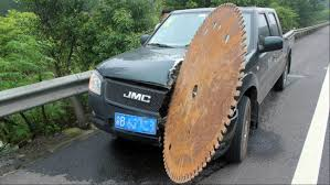 enormous saw blade rolls onto highway rips into truck photo