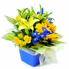 flowers in a box table flowers arrangement of yellow roses lilies and blue