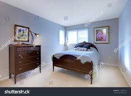 blue bedroom dark wood bed dresser stock photo 113307523