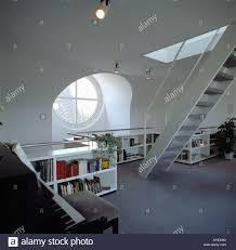 circular window above low bookshelves in modern white loft