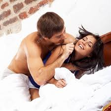 young happy couple having a pillow fight in a bed stock photo