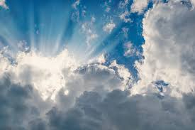 white fluffy clouds with sun rays background the horizontal frame