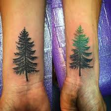 black and green pine tree tattoos on forearm
