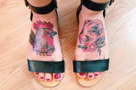 rooster and pig head with flower tattoos on feet