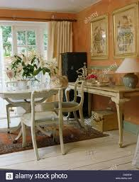 white painted table and chairs in peach cottage dining room with
