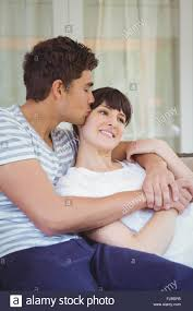 young couple cuddling on sofa stock photo royalty free image