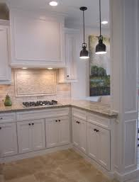 kitchen with off white cabinets stone backsplash and bronze