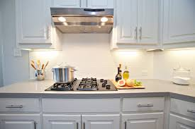 resplendent white kitchen backsplash with black iron gas fire top