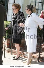 nancy reagan with a walking stick leaving a medical building in