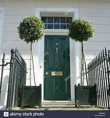 Black And White Planters by Traditional White Townhouse With Clipped Bay Trees In Black