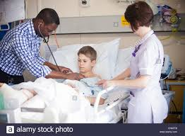 Doctor And Nurse A Young Boy Is Checked By A Doctor And Nurse On A Children U0027s