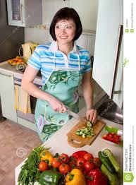 fait de la cuisine légumes de découpage de femme dans la cuisine image stock image