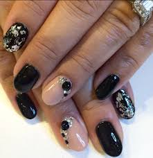 black and beige nail design with gold foil rhinestones and gold