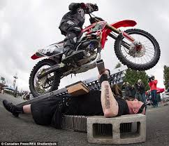 stuntman burnaby q orbax is run over by 70 motorcycles on a bed