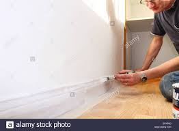 Skirting Board For Laminate Flooring Man Painting Skirting Board In A Uk Home Stock Photo Royalty Free