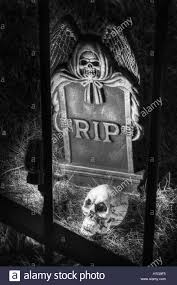 rip tombstone with skull behind fence halloween decorations