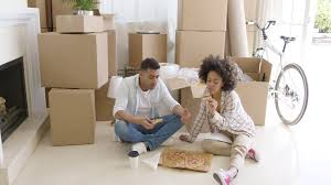 hungry young couple eating a pizza on the floor of the living room