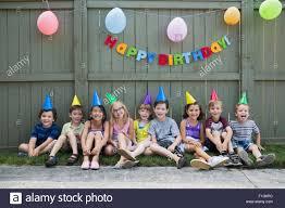 portrait smiling kids a row backyard birthday party stock photo