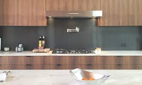 cropped kitchen cabinets made with walnut and metal backsplash and stone counter jpg