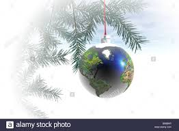 world globe ornament hanging from a tree stock photo