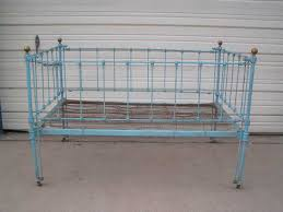this is an antique cast iron baby bed with brass knobs on the