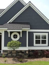 dark blue grey vinyl siding on a house with stone veneer around
