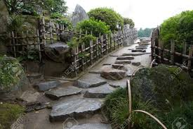 stepping stone path bordered by bamboo fence ascends slope in