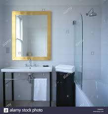 brass framed mirror above washbasin in modern tiled bathroom with