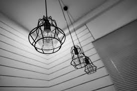 black steel framed round pendant lamp indoors near window blinds