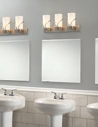 white cylinders vanity lights plus square mirror placed on the