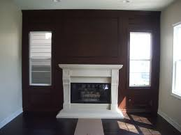 wainscoting on wall around fireplace with windows cabinet