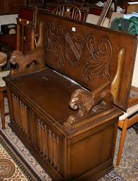 carved oak monks bench seat with lion arm rests and storage box