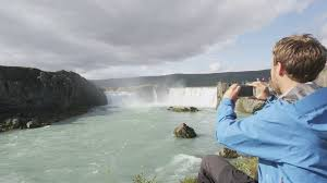 tourist taking photo with smartphone of waterfall godafoss on