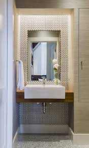 Ideas For Small Powder Room - wall of patterned tile with floating wood vanity