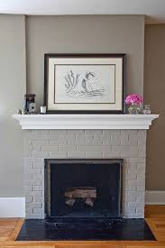 brick fireplace painted same color as surrounding walls warm gray with bright white details look good with the floor which is like