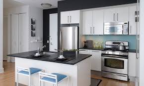 stainless steel appliances featuring white kitchen cabinets with